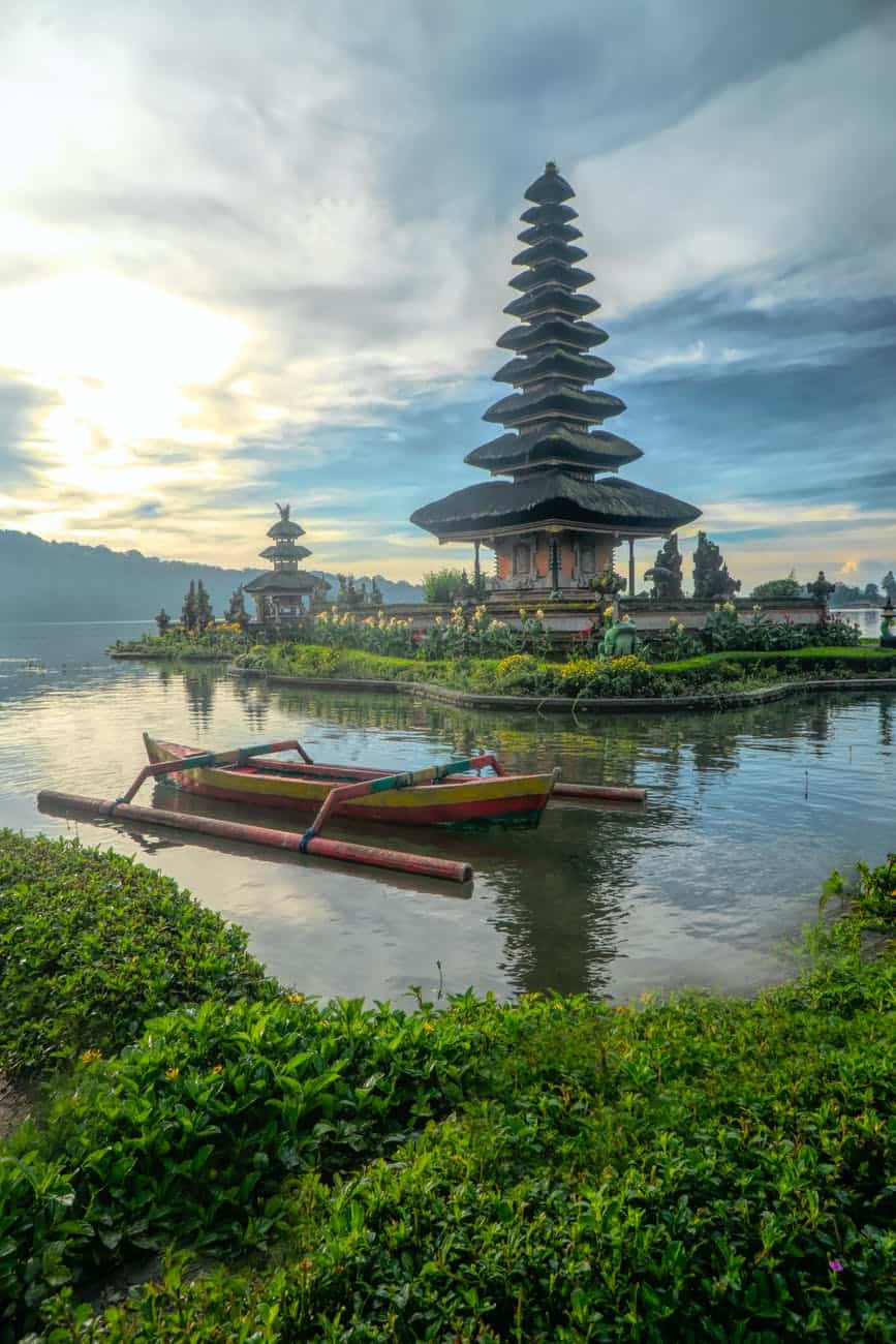 canoe on body of water with pagoda background